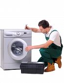 stock photo of dungarees  - A repairman holding a spanner and posing next to a washing machine isolated on white background - JPG