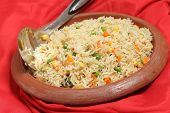 Vegetable pilau, or pulau, rice in an ethnic indian terracotta clay bowl with a rice serving spoon.