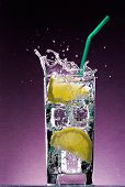 Sliced Lemon Falling In Glass Of Alcoholic Drink With Ice Cubes And Green Straw On Textured Violet B