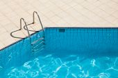 Blue swimming pool with metal ladder