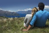 Rear view of a romantic couple looking over lake and hills