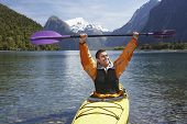 Cheerful man holding up kayak oar over head in mountain lake