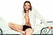 Handsome man in an unbuttoned white shirt sitting on a bed. Isolated over white.