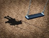 stock photo of swings  - Missing child concept with an empty playground swing and the shadow of a little girl on the park floor as a symbol of children losing their childhood and being lost as in a failed adoption or youth despair caused by family violence - JPG