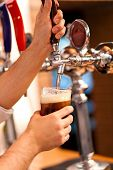 stock photo of drawing beer  - Barman brewing a beer - JPG
