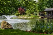 pic of manicured lawn  - Beautiful manicured garden with a deck overlooking a pond with a fountain that - JPG