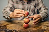 Man Trying To Balance Apples On Top Each Other