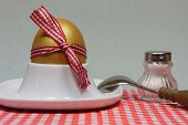 Golden Egg In An Egg Cup On A Red Patterned Napkin