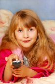 stock photo of goodnight  - young girl with remote control lying on the bed - JPG