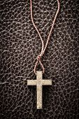 stock photo of leather-bound  - Closeup of simple wooden Christian cross necklace on leather bound holy Bible