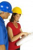 Female Architect and male contractor looking at building plans, gesturing towards some aspect of the