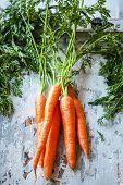 Fresh organic carrots an old wooden board