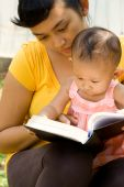 pic of babysitting  - portrait of mother babysitting curious baby girl during readings outdoor - JPG