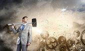 Young businessman with hammer against gears background