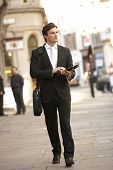 Businessman with tablet walking down street