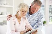 Senior couple using tablet at home