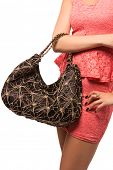 Closeup of woman with embroidered lace black evening bag. Wearing mini lace dress. Isolated on the w