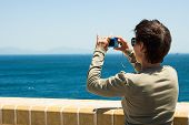 picture of gibraltar  - Tourist woman taking a picture of sea in Gibraltar - JPG