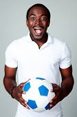 Funny african man holding soccer ball on gray background