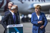 BERLIN, GERMANY - MAY 20, 2014: German Chancellor Angela Merkel (R) and Turkish Minister of transport Lutfi Elvan (L) open up the International aviation and space exhibition ILA.