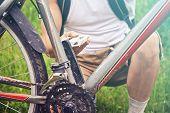 Man Checks Pedal Of Bicycle