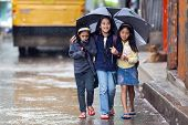 BANAUE, PHILIPPINES, DECEMBER 03 : Little girls are walking under the rain sheltering with an umbrel