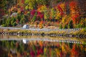 Camper driving though fall forest with colorful autumn leaves reflecting in lake. Highway 60 at Lake