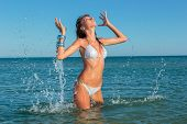 Beautiful woman jumps out of the sea leaving a big splash