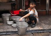 Boy Doing The Dishes On The Sidewalk.