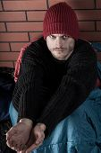 picture of sleeping bag  - Man in sleeping bag with cupped hands asking for money - JPG