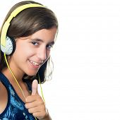Trendy hispanic teenager listening to music on her headphones while doing a thumbs up sign isolated