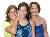 Hispanic girl with her mother and grandmother hugging and smiling isolated on white
