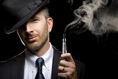 image of tobacco smoke  - male smoking a vapor cigarette as an alternative to tobacco - JPG