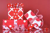 Stack Of Bright Red And White Polka Dot And Check Festive Christmas Gift Boxes On Red Background.