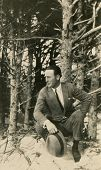 CANADA - CIRCA 1950s: An antique photo shows portrait of a a young man near the tree.
