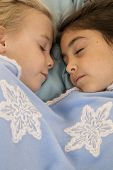 Portrait Of Two Beautiful Young Girls Asleep In Bed