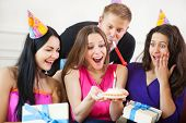 Girl Looking At Birthday Cake Surrounded By Friends At Party