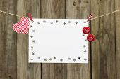Blank white snowflake sign with cherry soda pop caps and red heart by antique wooden background