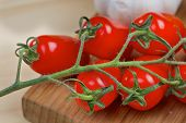 Bunch of cherry tomatos on a wooden board