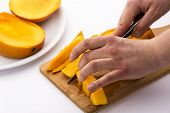 Mango Wedges Being Diced On A Wooden Cutting Board