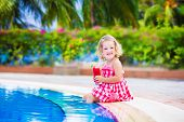 Little Girl Drinking Juice At A Swimming Pool