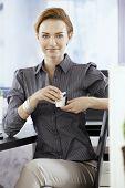 Happy young businesswoman having coffee-break in office.