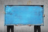 Two Businessman Holding Old Blue Blank Wooden Noticeboard