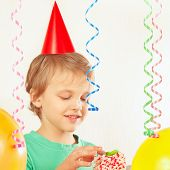 Little child in festive hat eating piece of birthday cake