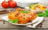pic of lasagna  - Portion of tasty lasagna on wooden table - JPG