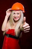 Portrait Of A Young Girl In A Santa Suit And Helmet Of The Builder Showing His Thumb