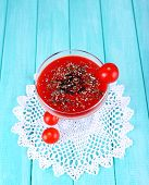 Tomato juice in glass goblet and fresh vegetables on lace napkin on wooden background