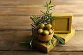 Bars of natural soap with rosemary and olive oil on wooden background