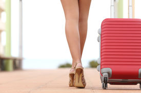 stock photo of red back  - Back view of a traveler woman legs walking with a suitcase in the street towards the beach with copyspace - JPG