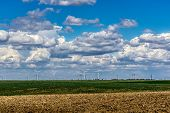 image of turbines  - Fluffy clouds over plowed field with eolian turbines - JPG